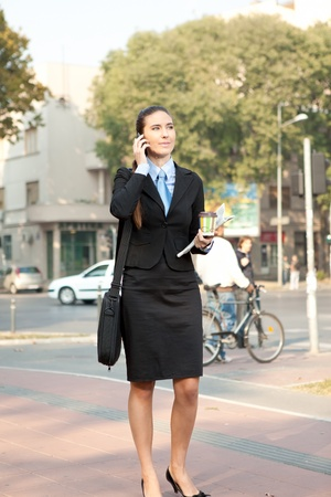 young attractive businesswoman on the phone walking on street, concept-city woman  photo