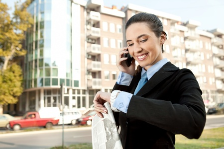 smiling businesswoman on the phone checking the time, concept-busy woman photo