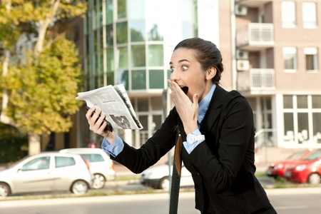 good news:  surprised businesswoman reading newspaper and  holding hand on mouth