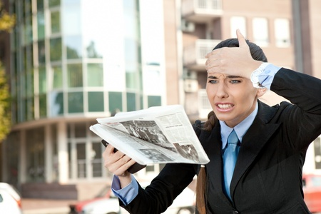 shocked woman reading newspaper on street, oh no bad news photo