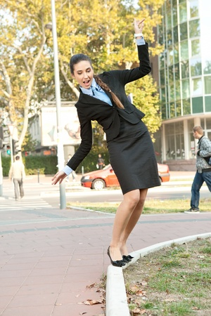 curb:  funny businesswoman balancing on  the curb, outdoor Stock Photo