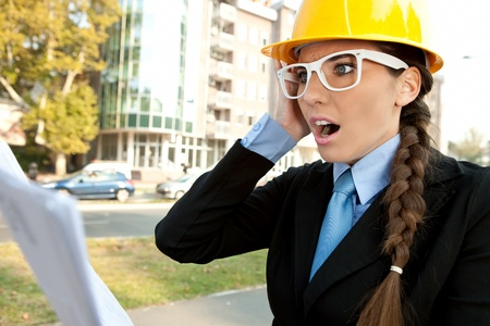 surprised female engineer reading  paperwork , shocked with information photo