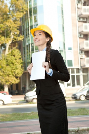 smiling female engineer holding paperwork, standing outside and looking up photo