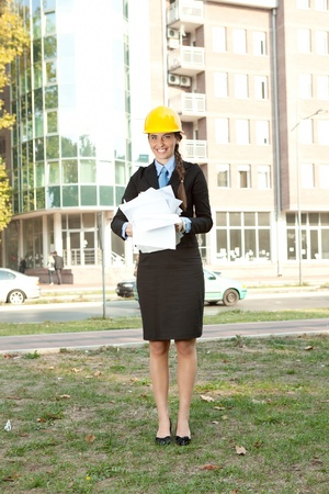 smiling female engineer holding  lot of documents, outdoor photo