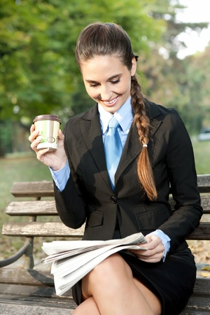 smiling business woman relaxing in park, reading newspaper and drinking coffee photo