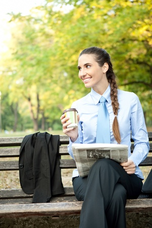 smiling young businesswoman with newspaper drinking coffee  photo