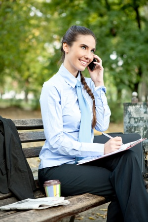smiling businesswoman sitting on bench ant talking on phone photo