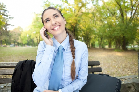 smiling beautiful businesswoman on phone, outdoor photo