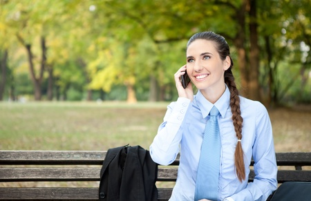 cheerful businesswoman relaxing in park and talking on phone photo