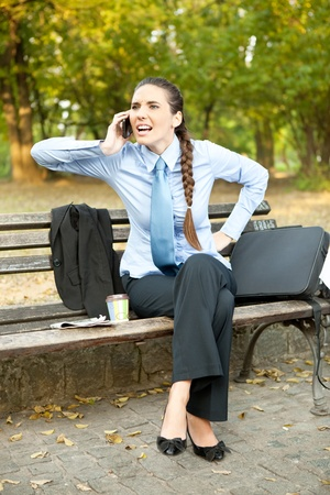 frustrate businesswoman sitting in bench in park and talking on phone photo