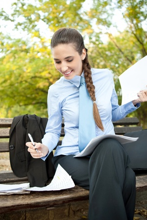 beauty businesswoman working with paperwork on bench in park Stock Photo - 11508061