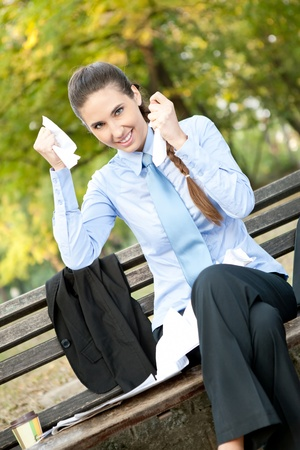 termination: ecstatic businesswoman sitting on bench in park tearing paper , termination of contract