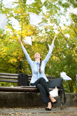 ecstatic: ecstatic businesswoman sitting on bench in park and  throwing paper in the air Stock Photo