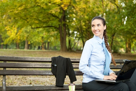 smiling, beautiful businesswoman working on bench in park photo