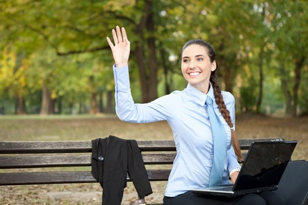 businesswoman working in park and waving hello photo