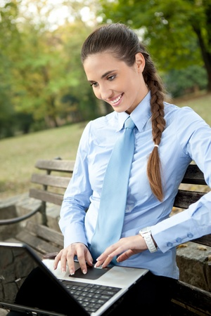 young businesswoman working on laptop in bench in park  photo