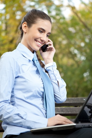 modern, young businesswoman working on laptop and talking on phone photo