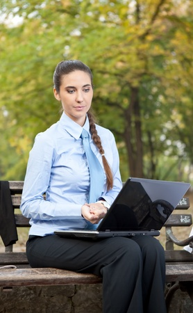 Serious businesswoman looking in lap top, outdoor photo