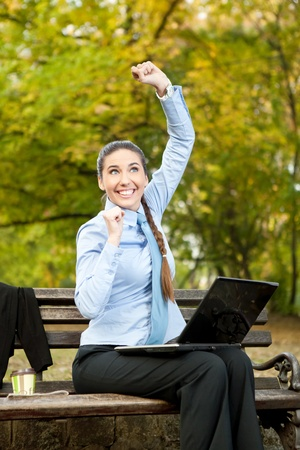 Excited businesswoman sitting on a park bench with laptop computer photo