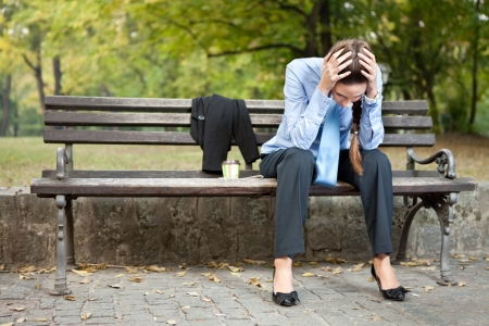 bankrupt: worried caucasian businesswoman sitting on bench in park