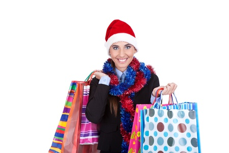 Shopping pretty young smiling woman in Santa hat holding shopping bags, isolated over white background. photo