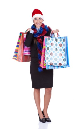 smiling girl holding shopping bags with christmas presents, isolated on white background photo