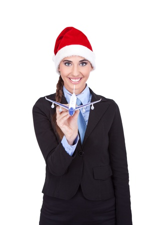smiling stewardess with Santa hat holding plane,  isolated on white background photo