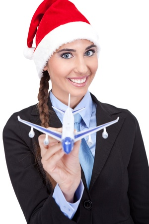 smiling santa businesswoman  holding  plane, concept - Christmas  travel, isolated on white background photo