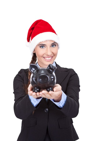 christmas savings: confident businesswoman with santa hat  holding piggy bank, concept - Christmas savings Stock Photo