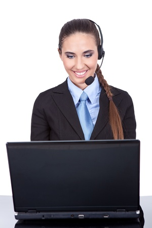 Young female operator works on  computer and receives phone calls on headset, isolated on  white background photo