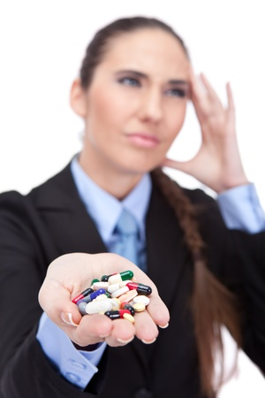 Portrait of a young businesswoman having a migraine and holding handful of pills, isolated on white background photo
