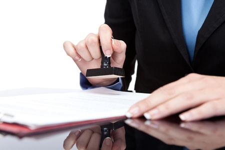 woman with document:  Young businesswoman (or notary public) seating at the desk in office and stamping document Stock Photo