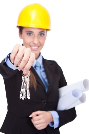 smiling young architect shoving  keys  of new house, isolated on white background photo