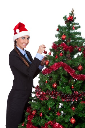 young woman in a christmas hat decorate a christmas tree, isolated on white background photo