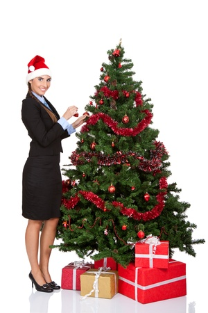 attractive girl decorating christmas tree, isolated on white background  photo