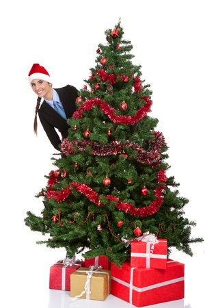 girl with santa hat peeking  behind christmas tree, isolated on white background  photo