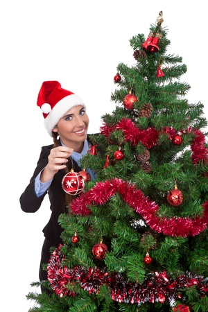 smiling woman putting christmas ball on  christmas tree, isolated on white background photo