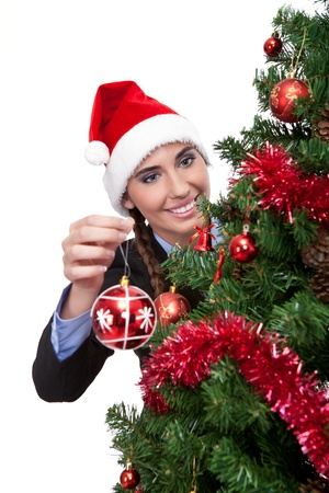 smiling woman decorating christmas tree with christmas ball, isolated on white background photo