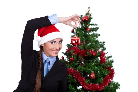 funny  woman decorating christmas tree with  christmas ball, isolated on white background photo