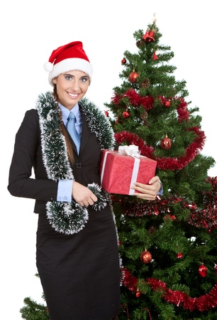 smiling woman holding boxing gift next christmas tree, isolated on white background photo