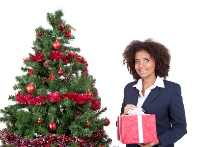 smiling afro woman holding gift box and standing next christmas tree, isolated on white background photo