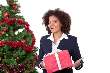 happy afro girl holding box gift in hands, in background christmas tree  photo