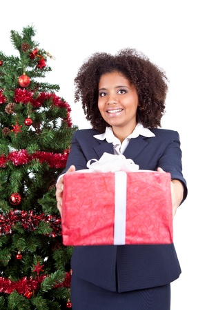 smiling afro woman showing  box gift, next christmas tree, isolated on white background photo