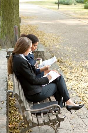 overworked businesswomen working on bench in park photo