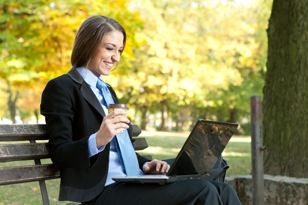 young , happy businesswoman looking in laptop, relaxing in park  photo