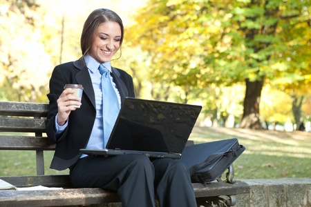 smiling businesswoman with coffee in hand looking in laptop, outdoor photo