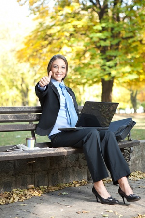 success pretty businesswoman  with thumb up, outdoor photo