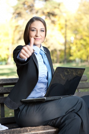 young pretty businesswoman  with thumb up, sitting on bench in park  photo
