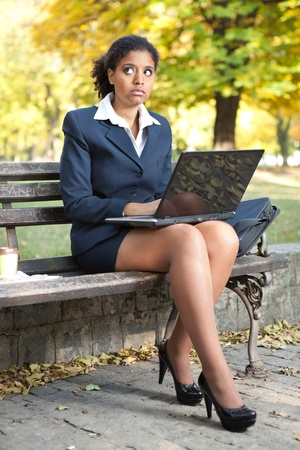 African American businesswoman with laptop , outside  photo