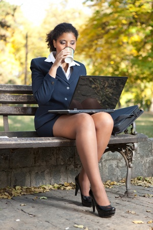 afro  business woman working on  laptop coffee break  in park photo